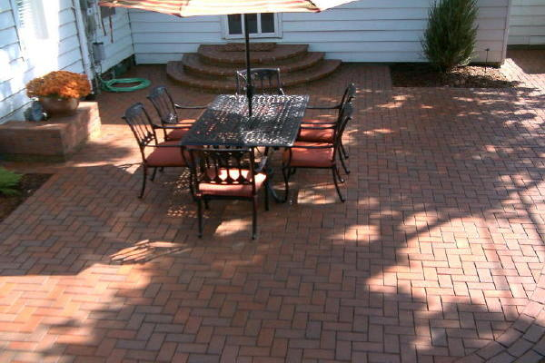 image of a paver patio featuring clay pavers, herringbone pattern and tripple running bond border. Pavers are Pine Hall Brick, English Edge, Autumn color.