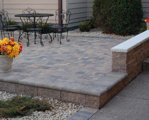 image of a paver patio featuring free standing walls. Random cobble pattern, bullnose border along raised portion. Pavers Type: Cobble Series, Paver Color: Chestnut and Lakeshore blends.
